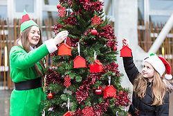 """Campaigners from Shelter Scotland raise awareness of their campaign """"Homelessness - Far From Fixed"""" outside the Scottish Parliament in Edinburgh. They are joined by carol singers from Corstorphine Primary School, a Christmas tree and a giant snakes and ladders board game - Chance Not Choice - which illustrates how life chances affect people's ability to keep a roof over their head.<br /> <br /> Pictured:Emma Willson from Corstorphine Primary School and Izzy Gaughan from Shelter"""