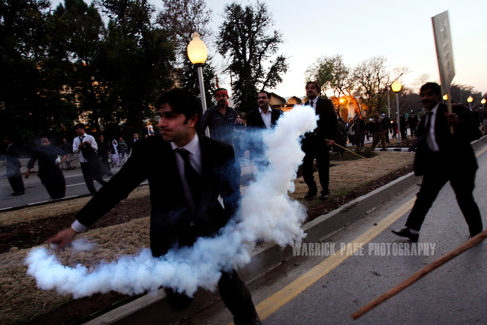 ISLAMABAD, PAKISTAN - FEBRUARY 9: A lawyer prepares to throw a  tear-gas canister back at police during an anti-government demonstration near the home of the deposed chief justice, Iftikar Chaudry  February 9, 2008 in Islamabad Pakistan. Police used water-canons and tear gas to repel demonstrators as they attempted to march to the home of the former chief justice who remains under house arrest since November last year. Pakistanis will go to the polls later this month after months of political and civil turmoil. (Photo by Warrick Page)