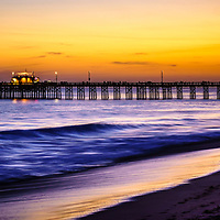 Picture of Balboa Pier at Sunset in Newport Beach California. Balboa Pier is located on Balboa Peninsula  along the Pacific Ocean in Orange County Southern California. The pier is a popular attraction for fishing and the Ruby's Diner restaurant at the end of the pier.