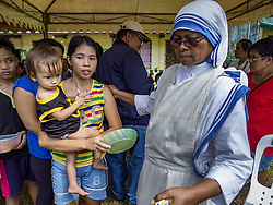 January 29, 2018 - Camalig, Albay, Philippines - A nun with the Missionaries of Charity helps an evacuee from Barangay Gapo in a small shelter for people evacuated from Mayon volcano in Camalig. The Missionaries of Charity visited the shelter to hand out food and clothes. A woman at the shelter said they were out of clean drinking water and several people had come down with diarrhea and other stomach ailments. There are only 206 people at the shelter, many of the shelters have over 1,000 residents. Mayon volcano's eruptions continued Monday. At last count, more 80,000 people have been evacuated from their homes of the slopes of the volcano and are crowded into shelters in communities outside of the danger zone. (Credit Image: © Jack Kurtz via ZUMA Wire)