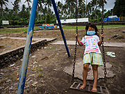 "22 JANUARY 2018 - GUINOBATAN, ALBAY, PHILIPPINES: A girl at Muladbucad Grande Elementary School in Guinobatan wears a face mask while she plays on the swings. Several communities in Guinobatan were hit ash falls from the eruptions of the Mayon volcano and many people wore face masks to protect themselves from the ash. There were a series of eruptions on the Mayon volcano near Legazpi Monday. The eruptions started Sunday night and continued through the day. At about midday the volcano sent a plume of ash and smoke towering over Camalig, the largest municipality near the volcano. The Philippine Institute of Volcanology and Seismology (PHIVOLCS) extended the six kilometer danger zone to eight kilometers and raised the alert level from three to four. This is the first time the alert level has been at four since 2009. A level four alert means a ""Hazardous Eruption is Imminent"" and there is ""intense unrest"" in the volcano. The Mayon volcano is the most active volcano in the Philippines. Sunday and Monday's eruptions caused ash falls in several communities but there were no known injuries.    PHOTO BY JACK KURTZ"