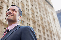 Businessman smiling outdoors low angle view