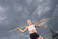 Female athlete holding javelin on shoulders low angle view
