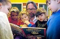 Primary school teacher reading to students.