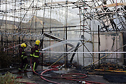 A London Fire fighter dampens down with a high-pressure hose after an inner-city estate fire in south London. About 310 people were forced to leave their homes after the fire engulfed a wooden structure under construction in scaffolding at Sumner Road and Garrisbrooke Estate, Peckham, London at about 0430 AM. It spread to two blocks of maisonettes and a destroyed a pub. More than 150 firefighters tackled this unusually large and ferocious fire which injured ten people, including two police officers who received hospital treatment for minor injuries.  .