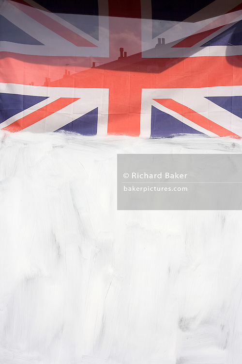 A Union Jack flag hangs above white emulsion paint which has been smeared over a shop window, a victim of the UK recession.