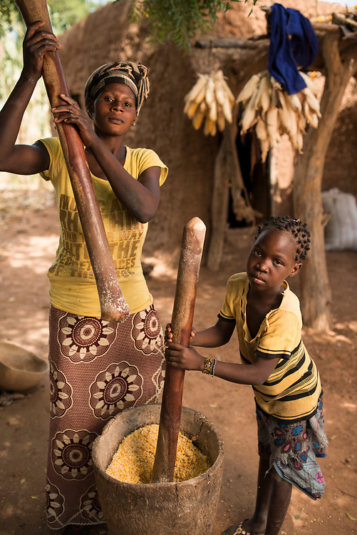 Grinding corn (maize) into meal for cooking in the village of Bagui Traue, near Kolokani, Mali.