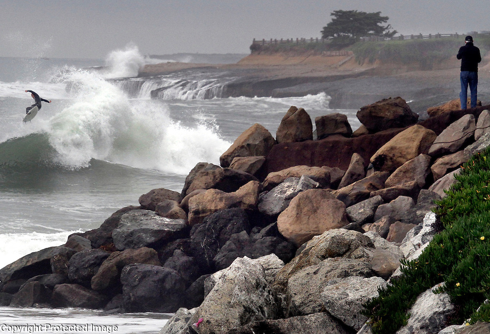 Mark Millenacker stands atop the bluff at the end of 20th Avenue in Santa Cruz, California to capture video of the storm-fueled waves beginning to roll into the Central California coastline as a surfer grabs some air at the end of a ride on December 10, 2014.