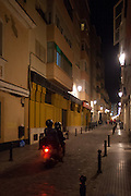 Motor scooter noisily hurtles down a narrow street at night in Cadiz, Spain