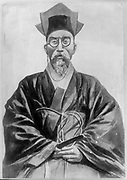 Kojong, Emperor of Korea (1852-1919). Three-quarter length portrait of Emperor, wearing spectacles, seated looking forwards.