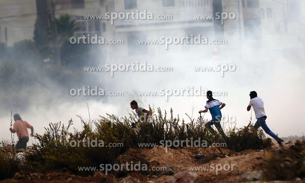 19.10.2015, Ramallah, PSE, Nahostkonflikt zwischen Israel und Pal&auml;stina, im Bild Zusammenst&ouml;sse zwischen Pal&auml;stinensischen Demonstranten und Israelischen Sicherheitskr&auml;fte // Palestinian protesters run for cover from tear gas during clashes with Israeli borderguards next to the Jewish settlement of Beit El. More than two weeks of unrest have raised warnings of the risk of a full-scale Palestinian uprising, while some Israeli politicians have urged residents to arm themselves to fend off the threat of stabbings and gun assaults, Palestine on 2015/10/19. EXPA Pictures &copy; 2015, PhotoCredit: EXPA/ APAimages/ Shadi Hatem<br /> <br /> *****ATTENTION - for AUT, GER, SUI, ITA, POL, CRO, SRB only*****