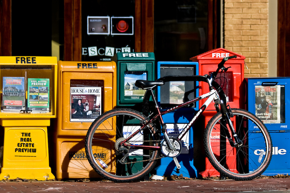 A bicycle locked up in front of free newspaper dispensers in Charlottesville, Virginia.