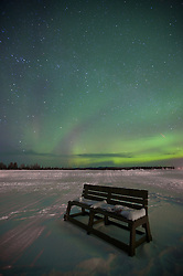 A bench waits for stargazers below the northern lights in the Arctic Circle.