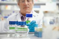 Scientist looking at specimen bottle in laboratory focus on bottle