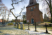(MODEL RELEASED IMAGE) For Sunday brunch outside Hamburg, Germany, Jörg Melander rides his bicycle through late-November snow to get rolls and pastries from a bakery near his home, passing by the 13th Century Lutheran Church in the town square. (Supporting image from the project Hungry Planet: What the World Eats.)