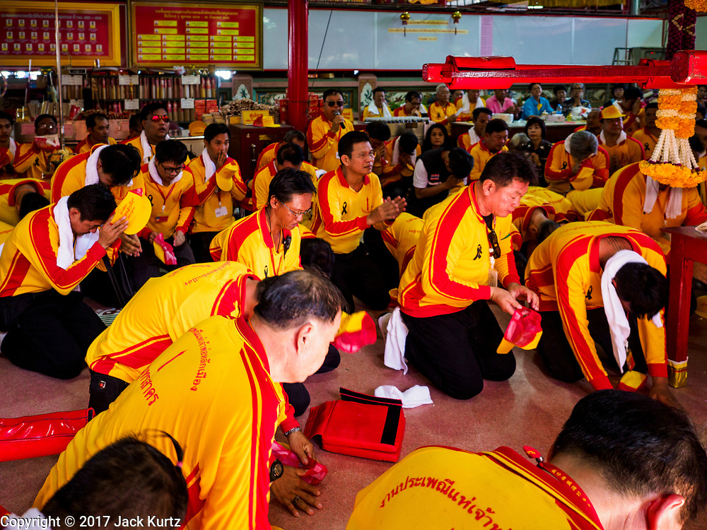 "02 JUNE 2017 - SAMUT SAKHON, THAILAND: Men pray before the City Pillar Shrine parade in Samut Sakhon. The Chaopho Lak Mueang Procession (City Pillar Shrine Procession) is a religious festival that takes place in June in front of city hall in Samut Sakhon. The ""Chaopho Lak Mueang"" is  placed on a fishing boat and taken across the Tha Chin River from Talat Maha Chai to Tha Chalom in the area of Wat Suwannaram and then paraded through the community before returning to the temple in Samut Sakhon. Samut Sakhon is always known by its historic name of Mahachai.      PHOTO BY JACK KURTZ"
