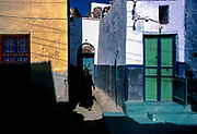 A Nubian woman, dressed in black, emerges from her brightly painted  home on Elephantine Island, Aswan.