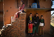 Tulachi, 15, Jandhara, 15, and Amana, 14, pose for a photo in front of the entrance to their extended family's chaupadi shelter, a squat crawlspace under the home where the women of the household sleep during their periods, in Rima village, Achham, Nepal. They share the space with the household's herd of goats.