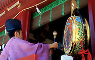 Shinto priest, banging drums during a wedding ceremony at Tsurugaoka Hachimangu Shrine in Kamakura.