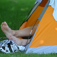 A rider rests in a tent at the park in De Smet during the Argus Leader Tour de Kota.