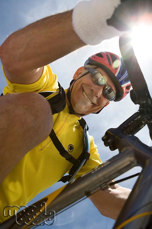 Senior man cycling, low angle view