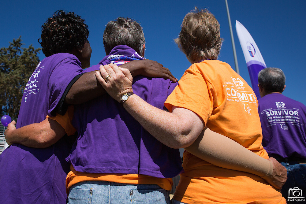 Survivors and supporters pray together during the opening ceremony of Relay For Life at the Milpitas Sports Center in Milpitas, California, on June 22, 2013. (Stan Olszewski/SOSKIphoto)