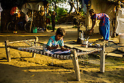24th March 2014, Shakarpur, New Delhi, India. 9 year old Ravi Kumar does his homework on a charpoy at his home on the Yamuna Bank  New Delhi, India on the 24th March 2014. Kumar attends a makeshift school under a metro bridge near the Yamuna Bank Metro station in Shakarpur.<br /> Rajesh Kumar Sharma (born 01/02/1970), started this makeshift school in 2011. Six mornings a week he teaches underprivileged children for three hours while his younger brother replaces him at his general store in Shakarpur. His students are children of labourers, rickshaw-pullers and farm workers. This is the 3rd site he has used to teach under privileged children in the city, he began in 1997. <br /> <br /> PHOTOGRAPH BY AND COPYRIGHT OF SIMON DE TREY-WHITE<br /> + 91 98103 99809<br /> email: simon@simondetreywhite.com