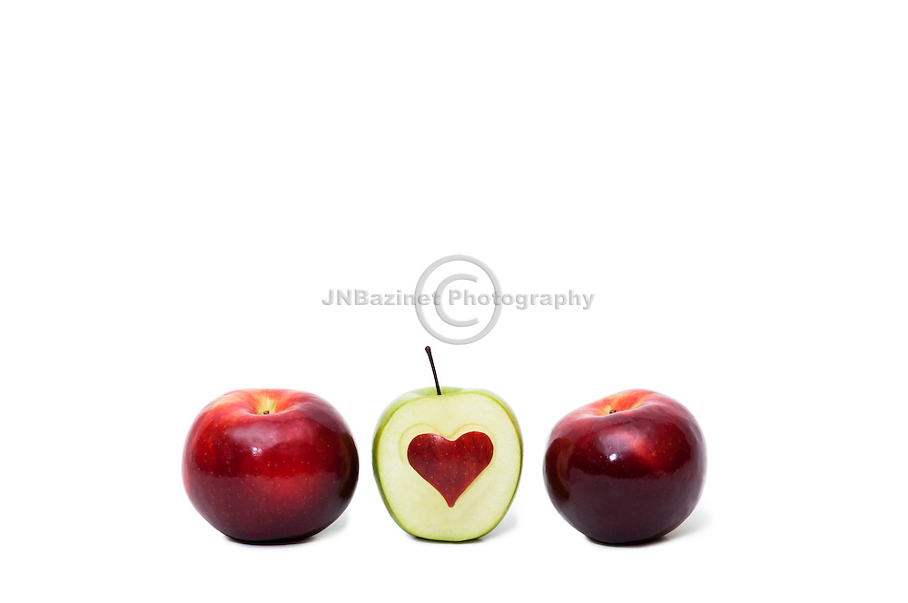 Three apples, one with heart shaped cutout symbolizing healthy eating