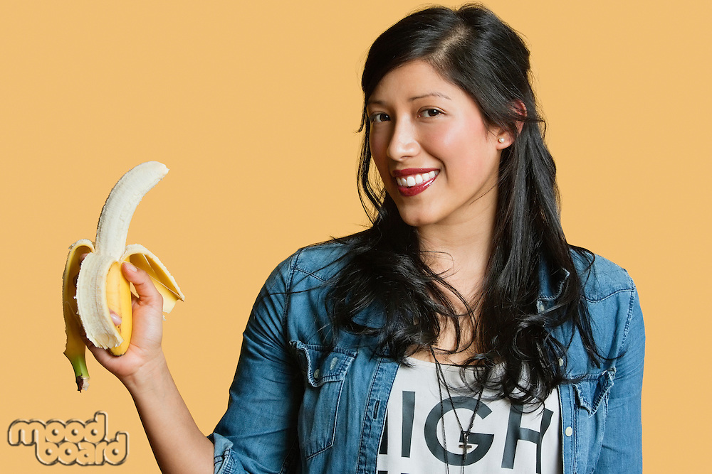 Portrait of a young woman with banana over colored background
