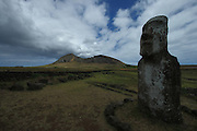 A moai stands near Tongariki, in front of the Rano Raraku volcano, along Easter Island's southern coast; clouds gather over the volcano