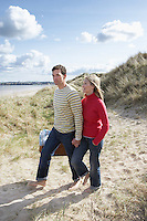 Couple holding hands walking on sand dune