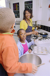 Single mother with young son and daughter cooking in kitchen,