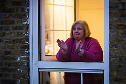 © Licensed to London News Pictures. 02/04/2020. London, UK. A woman is seen applauding from a flat balcony this evening on an estate in Wapping, east London during the 'clap for the NHS' and 'clap for carers' campaigns held in support of the NHS, as the spread of the coronavirus continues. Photo credit: Vickie Flores/LNP