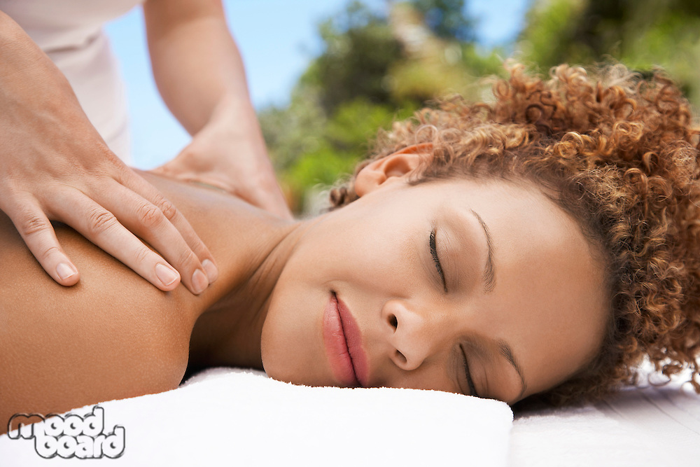 Woman receiving massage head and shoulders eyes closed