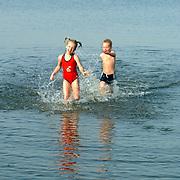 Kinderen spelen, rennen in het water Gooimeer, warme herfstdag