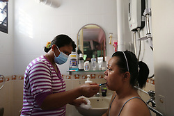 Indonesian domestic helper brushes Aishah's teeth in her home bathroom in Singapore, 21 July 2014. Having her teeth brushed properly became an important ritual in Aishah's life after losing her limbs as her smile became more important to her than ever.