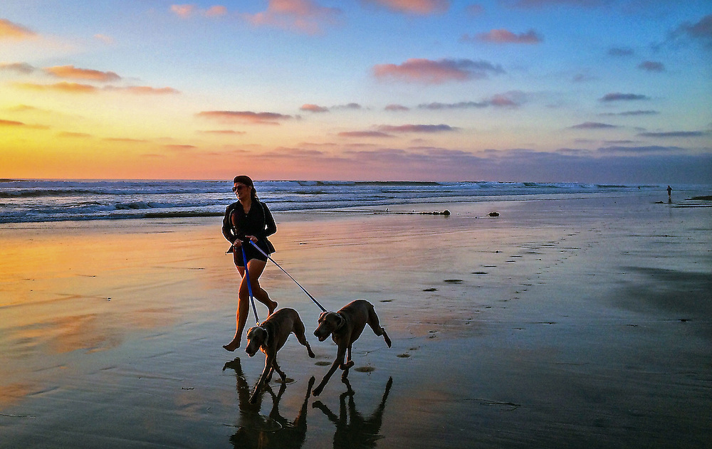 Woman running on beach at Del Mar at sunset with two dogs.