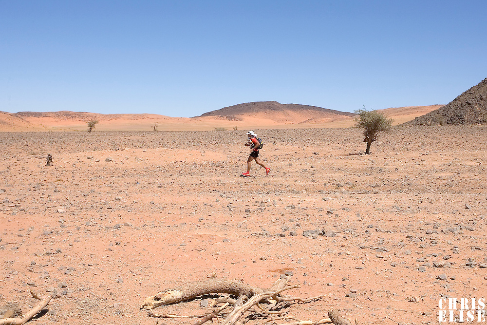 27 March 2007: A participant runs across hills and stony ground during third stage of the 22nd Marathon des Sables between jebel El Oftal and jebel Zireg (20.07 miles). The Marathon des Sables is a 6 days and 151 miles endurance race with food self sufficiency across the Sahara Desert in Morocco. Each participant must carry his, or her, own backpack containing food, sleeping gear and other material.
