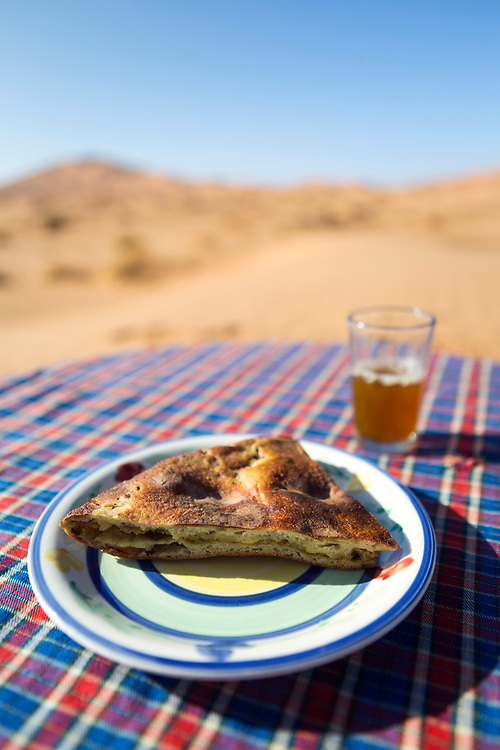 The limited resources of the Sahara's arid terrains means food needs to be easy to prepare. When a mud oven is not available, nomads use more rustic methods for cooking the stuffed bread by working with the only elements and resources available, such as fire and the sand, Merzouga, Southern Morocco, 2017-12-15.<br /><br />A small well is made in the sand and a fire heats stones placed at the base. Madfouna dough is added directly on top of the hot stones and covered with a metal tin or with the sand itself.<br /><br />Whether cooked using a mud oven or on hot rocks under the sands, a charred-black crust forms where the bread has directly touched the hot charcoals, and must be beaten off with a cloth and scraped away with a knife before eating.