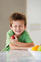 Young boy holding apple in kitchen