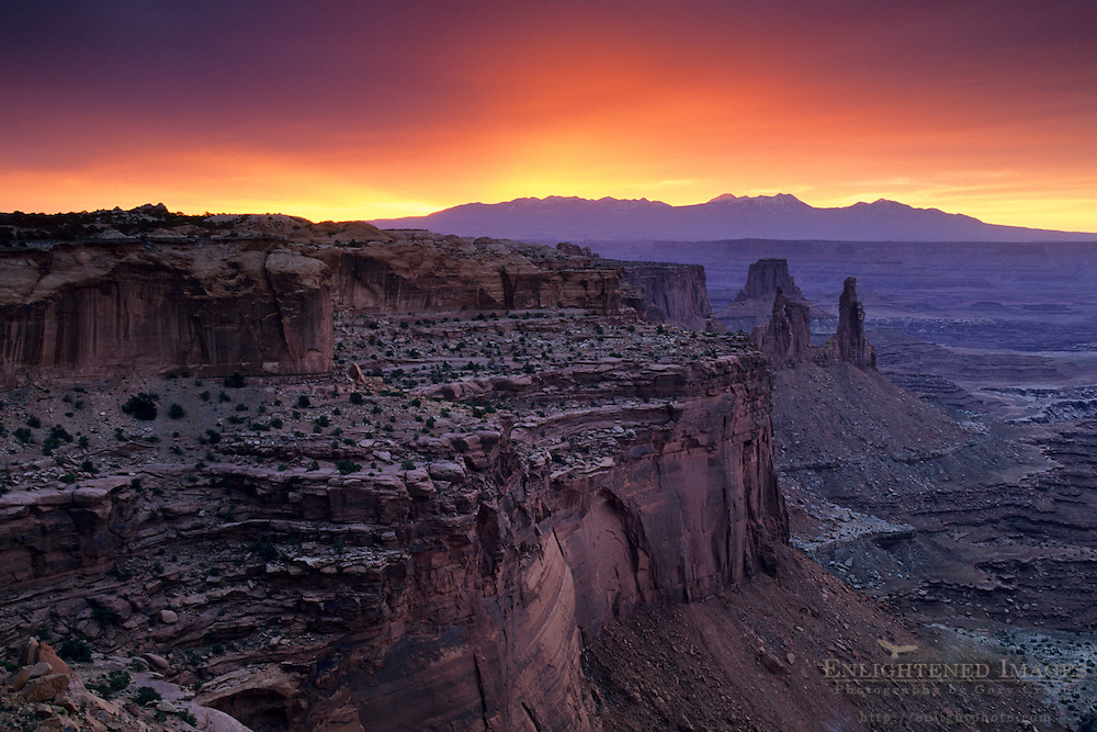 Stormy sunrise over the LaSal Mtns. and red rock cliffs from Mesa Arch, Island in the Sky, Canyonlands NP, UTAH