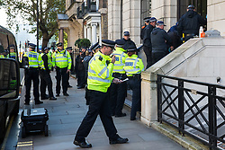 London, UK. 17 October, 2019. Metropolitan Police officers work to extract and arrest campaigners against the arms trade from Extinction Rebellion Scotland who had glued or locked themselves onto the entrance to the headquarters of Leonardo UK in protest against the company profiting from 'guidance systems for missiles used in Yemen and Syria, as well as other media technology and telecommunications' and in solidarity with the Kurdish people following the Turkish invasion of Kurdish-held areas of north-east Syria.