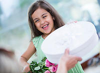 Portrait of cute girl holding gift box and flower basket at home