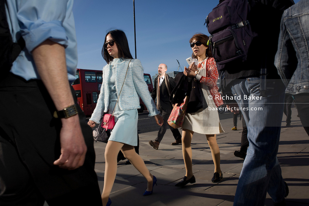 Londoners cross southbound over London Bridge during the evening rush hour.