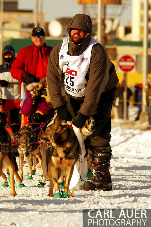3/3/2007:  Anchorage Alaska -  Rookie Richard Hum of Talkeetna, AK has to untangle one of his dogs during the Ceremonial Start of the 35th Iditarod Sled Dog Race.  He has a course hand hold the brake on his sled (in red jacket) while he tends to his dogs.