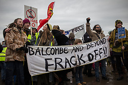 "© Licensed to London News Pictures . 26/01/2014 . Salford , UK . A banner that reads "" Balcombe and beyond frack off "" . Approximately 500 protesters march to an iGas fracking exploration site at Barton Moss , Salford , today (Sunday 26th January 2014) . They walk along the A57 road , blocking traffic as they do . A long term protest camp has been established on an access road leading to the site and today (26th January) protesters from other areas of the country travelled to the site to join with other protesters against fracking . Photo credit : Joel Goodman/LNP"