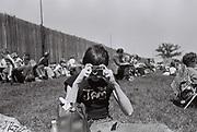 Boy in Jam t shirt with Kodak instamatic camera, Northampton, UK, 1980s.