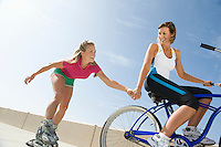 Young woman on bike pulling young woman on rollerblades