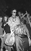 Man wearing round sunglasses in group of ravers dancing outside 1980s, UK.