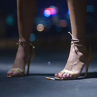 Young woman wearing evening shoes with high heels stamping on cigarette